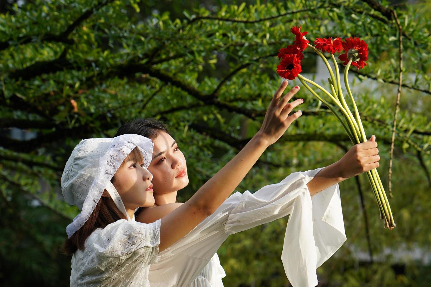 mujeres sosteniendo flores foto