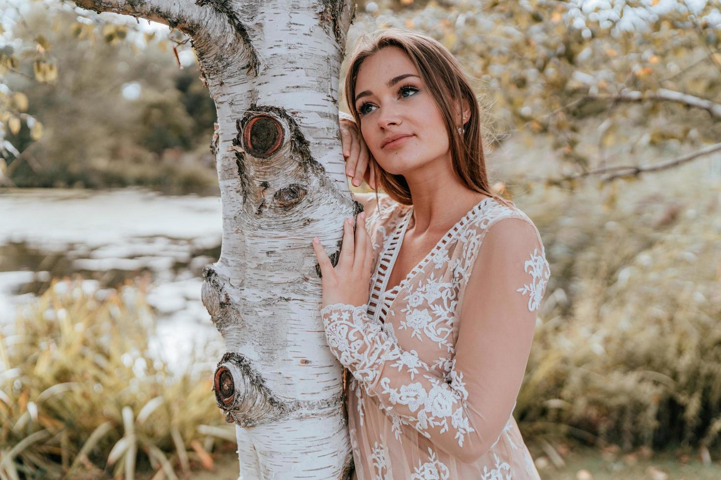 Woman leaning against a tree photo