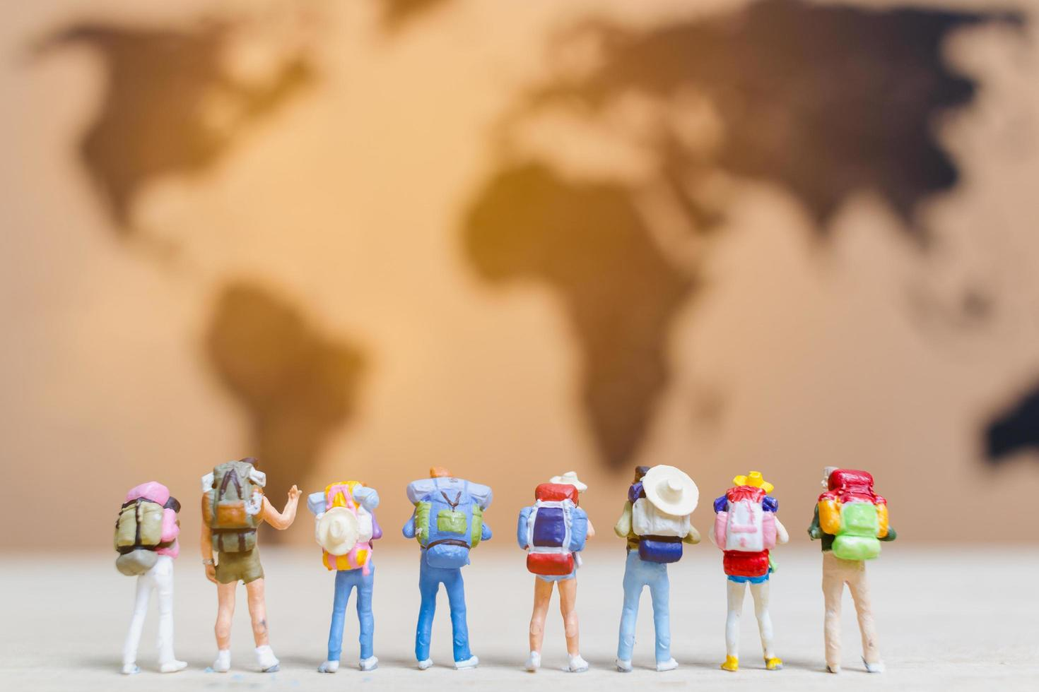 Miniature travelers walking on a world map, traveling and exploring the world concept photo
