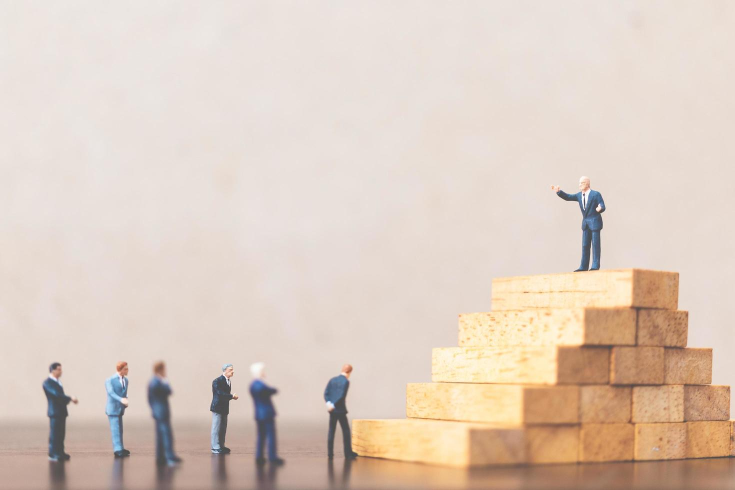 Miniature businessmen standing on a wooden block, successful business leader and teamwork concept photo
