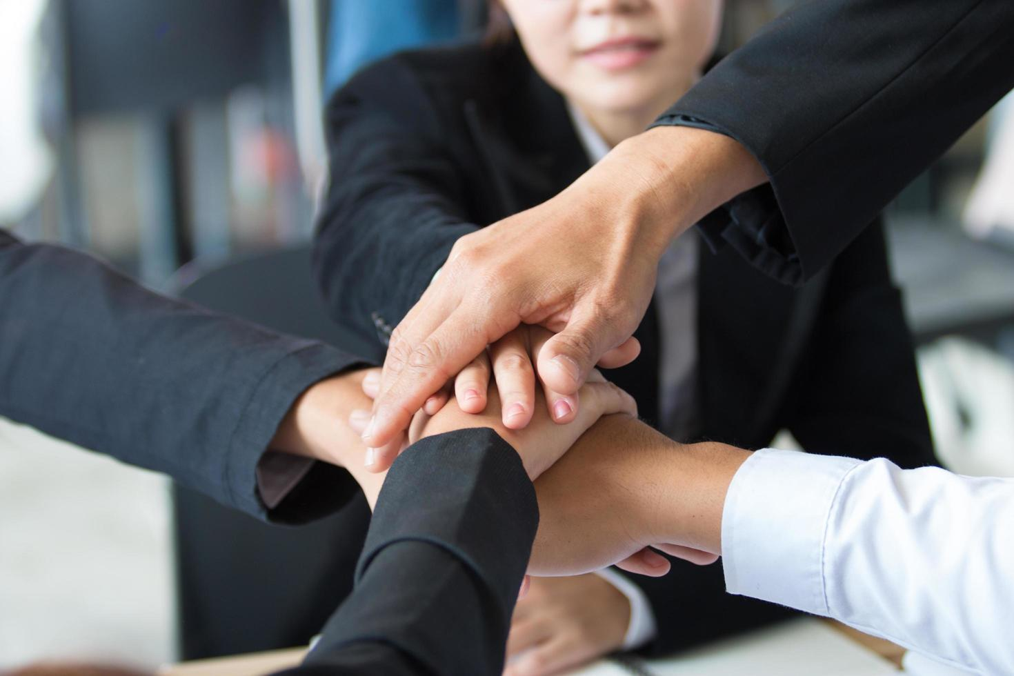 Close-up of young business professionals putting hands together photo