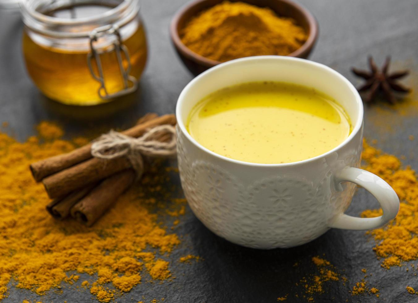 Golden milk with cinnamon, turmeric, ginger and honey over black concrete background photo