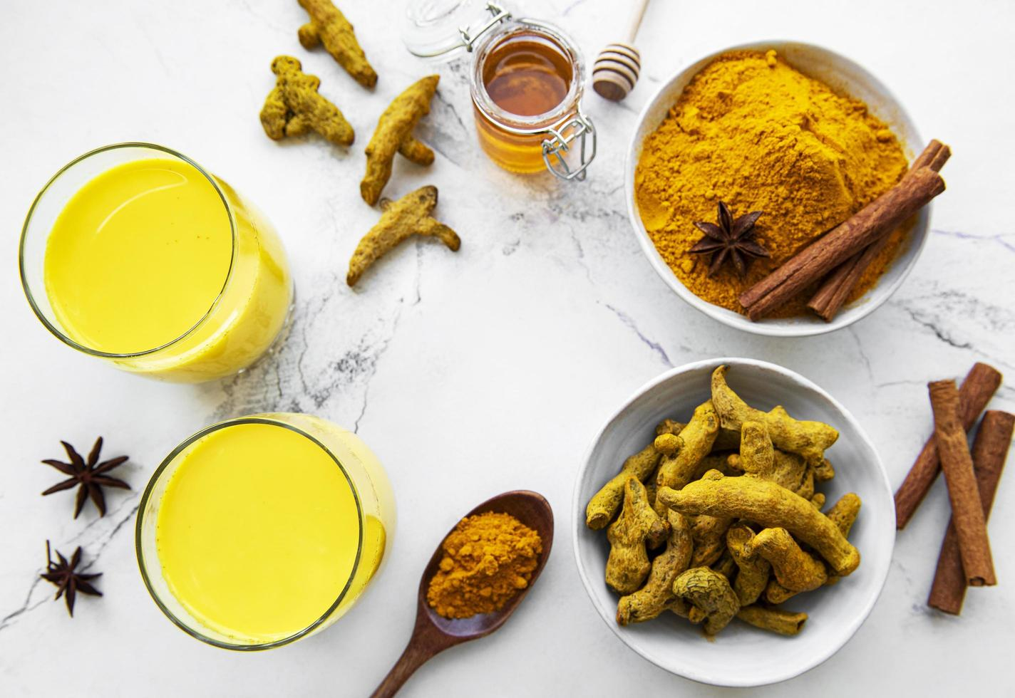 Golden milk with cinnamon, turmeric, ginger  and honey over white wooden background. photo
