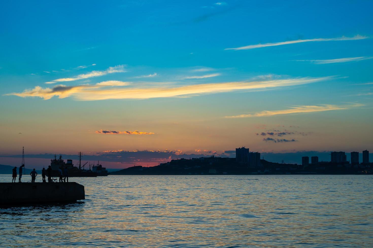 Paisaje marino con silueta de personas en un muelle con colorido atardecer nublado en Vladivostok, Rusia foto
