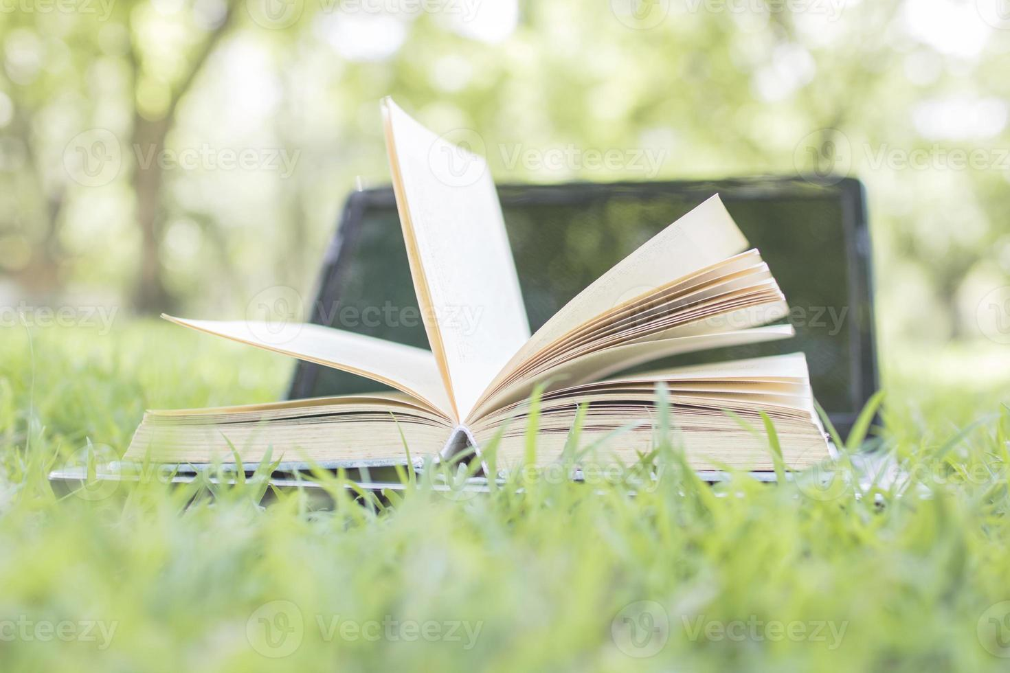 Book opening with laptop on green grass as freedom of knowledge concept photo