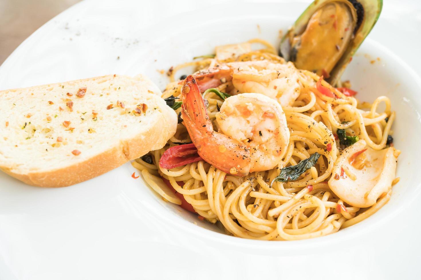 espagueti de mariscos en plato blanco foto