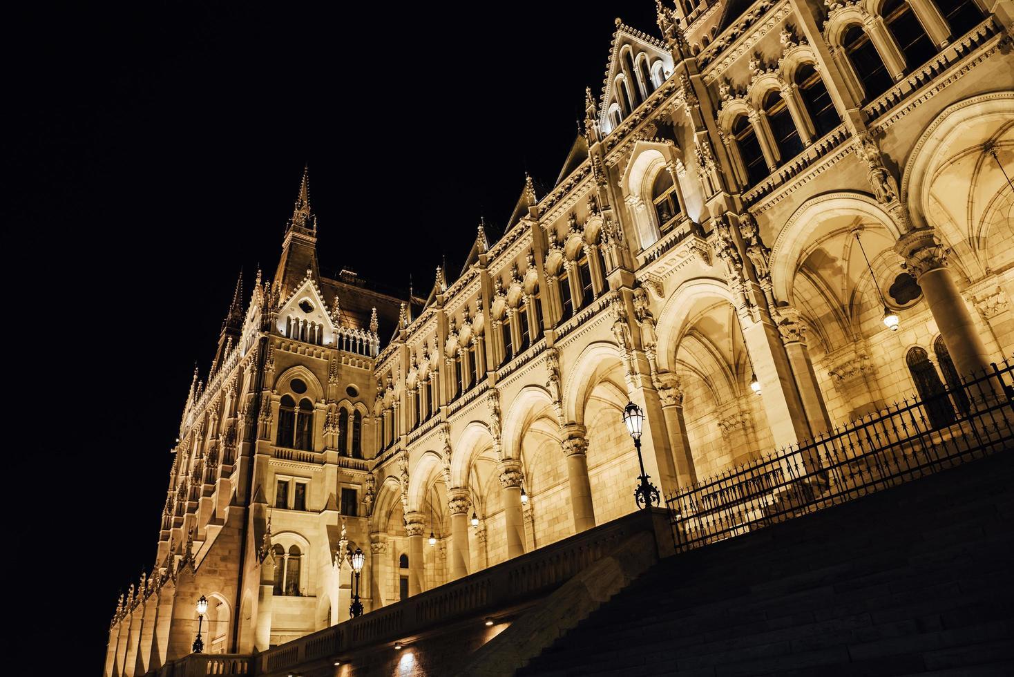 El parlamento húngaro en Budapest sobre el Danubio en las luces nocturnas de las farolas foto