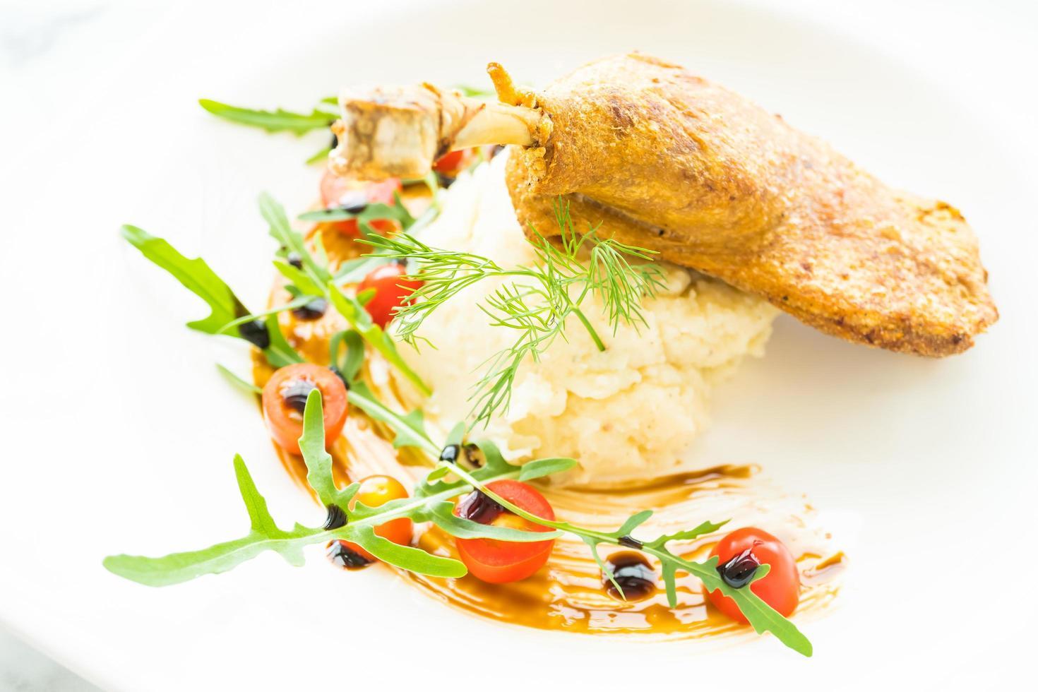 muslo de pato frito con ensalada de papas foto