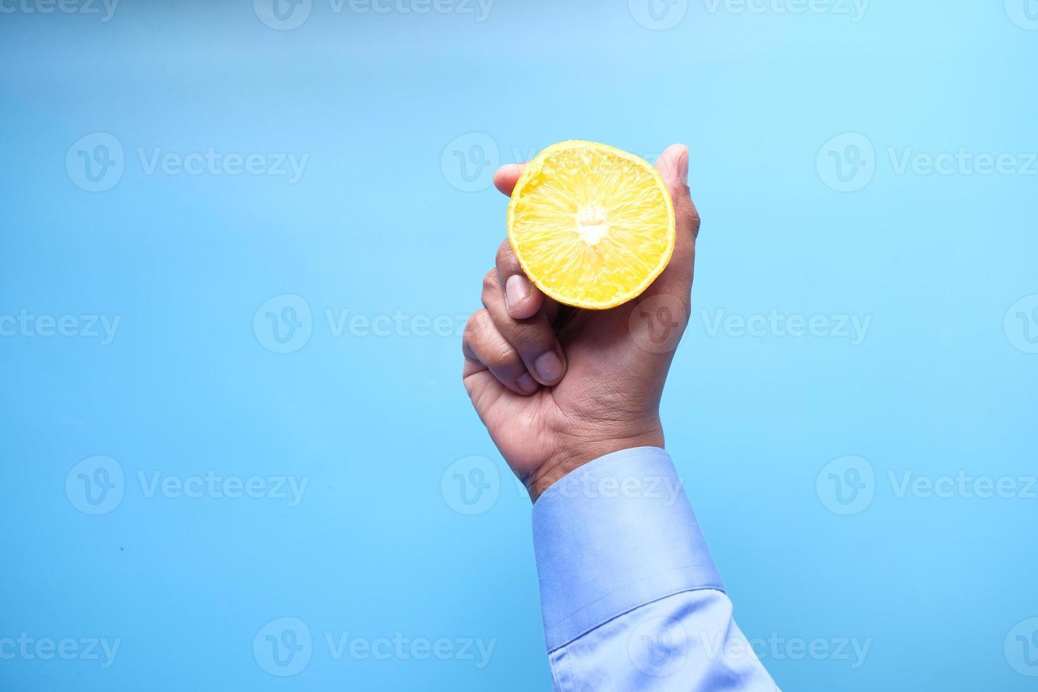 Hand holding citrus fruit on blue background photo