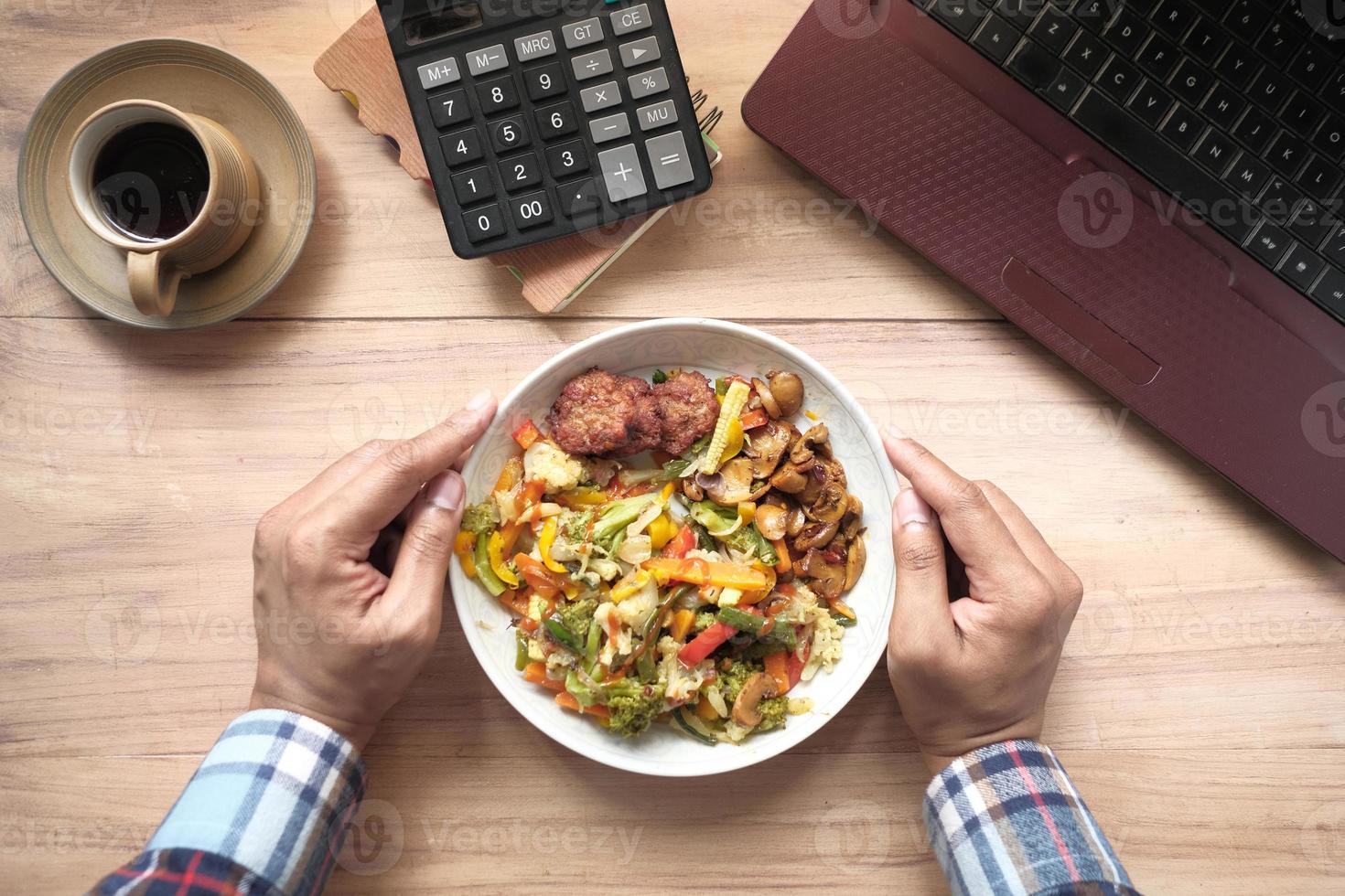 Persona comiendo salteados en la mesa de trabajo foto