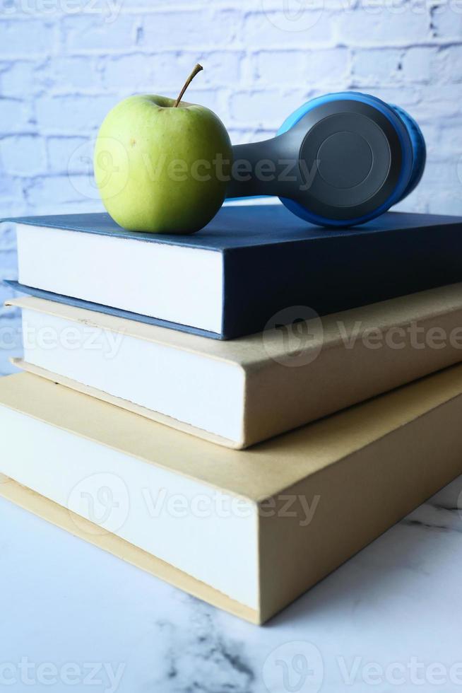 pila de libros, manzana y auriculares en la mesa foto