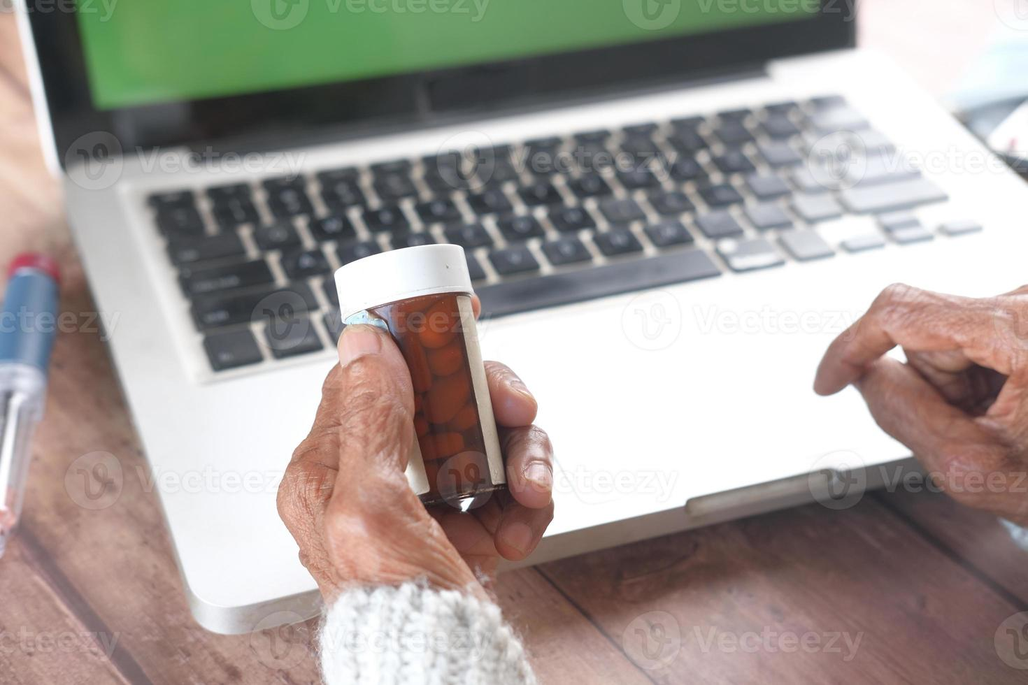 Mano de mujer sosteniendo el frasco de pastillas mientras está sentado frente a una computadora foto