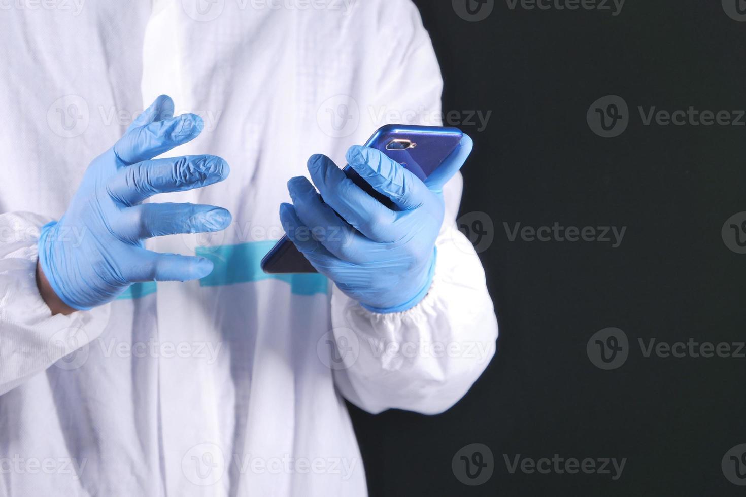 médico con teléfono inteligente sobre fondo negro foto