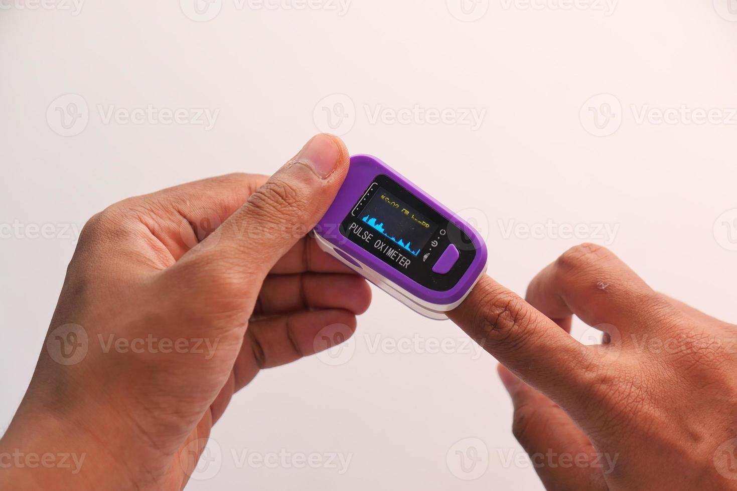 La mano del joven con pulsioxímetro foto