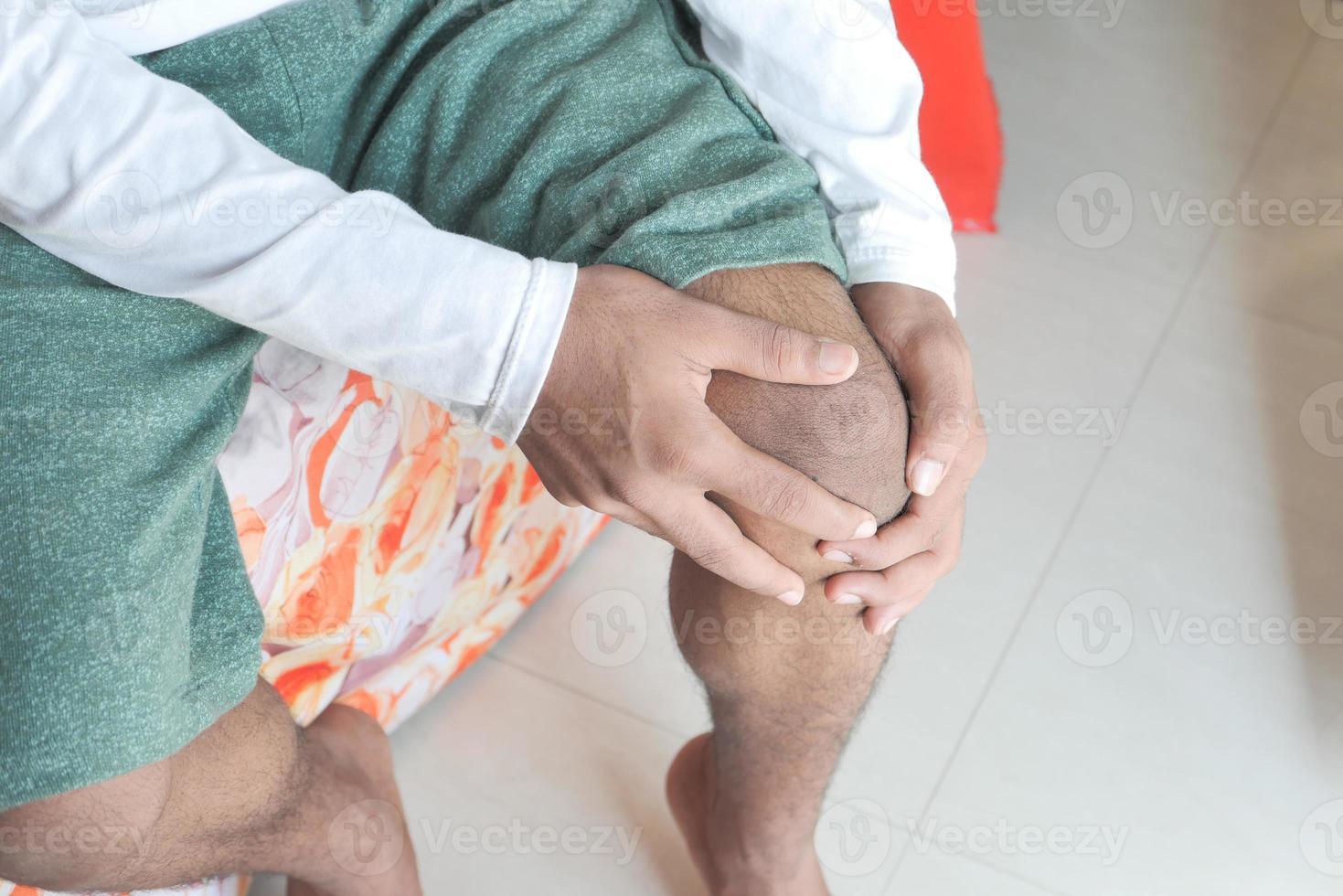 hombre sosteniendo la rodilla en el dolor foto