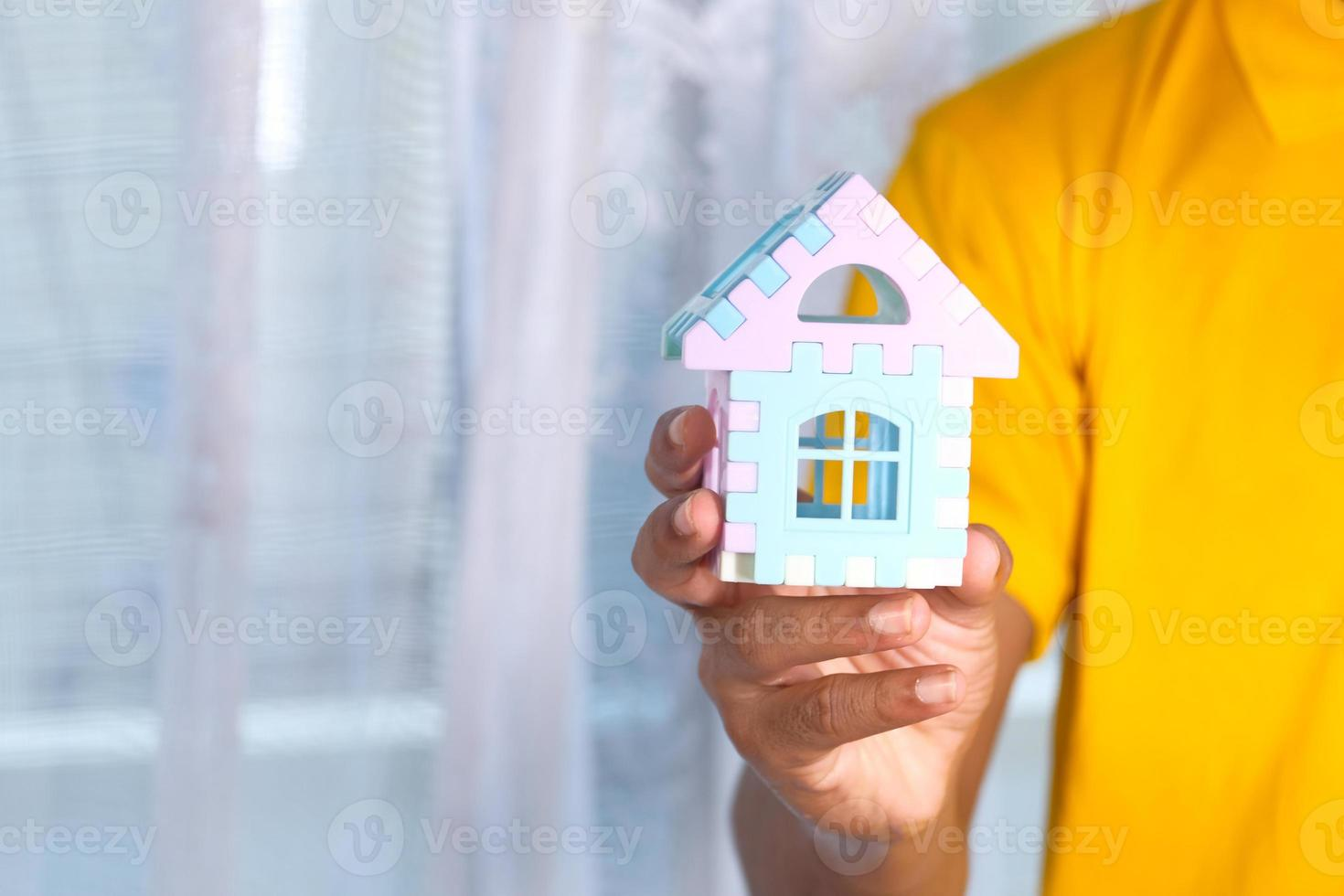 Man holding small toy house photo