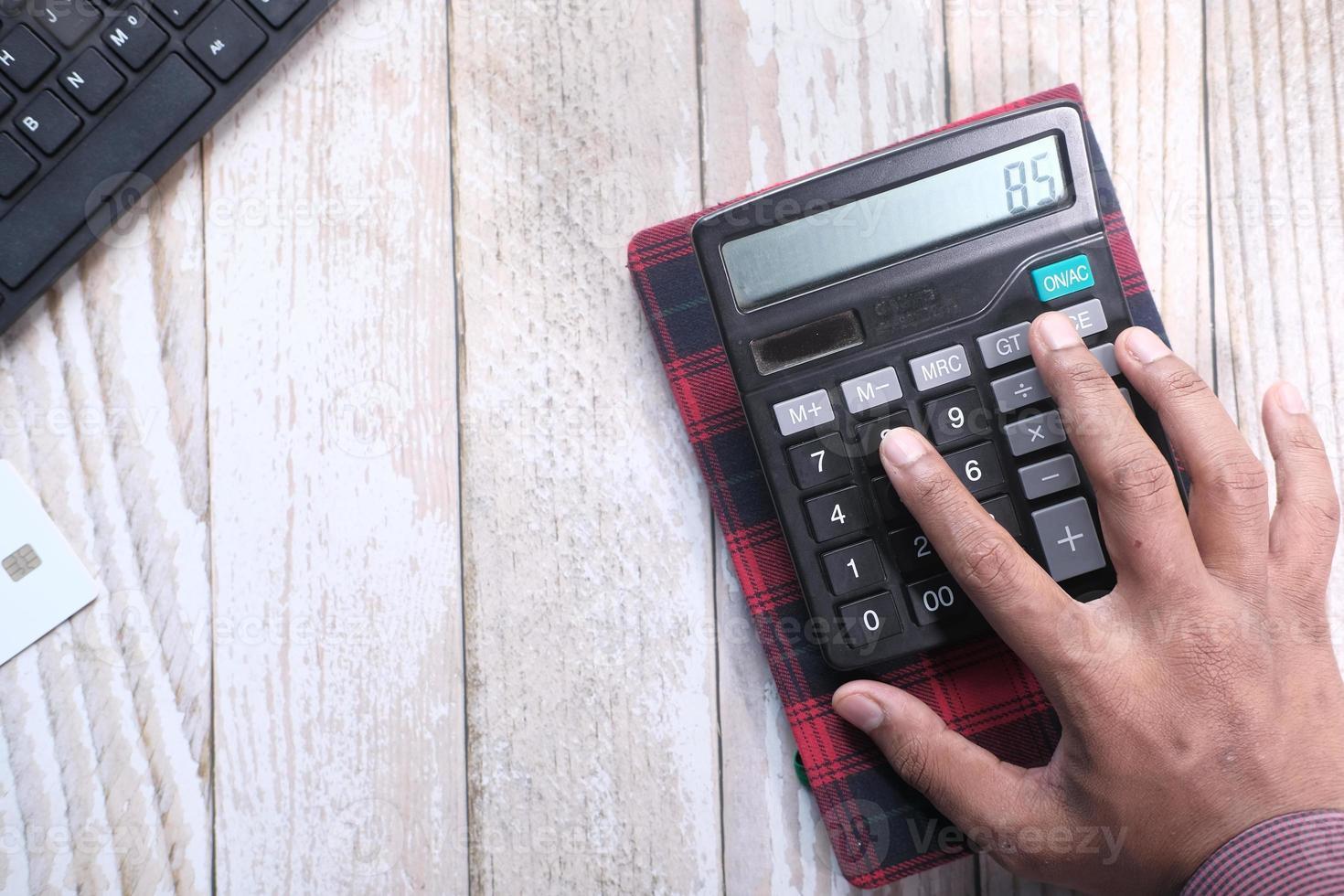Close up of man hand using calculator photo