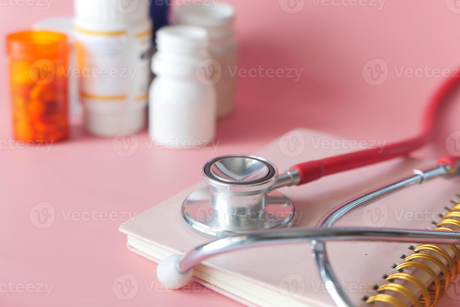 Envase de estetoscopio y pastillas sobre fondo de color rosa foto