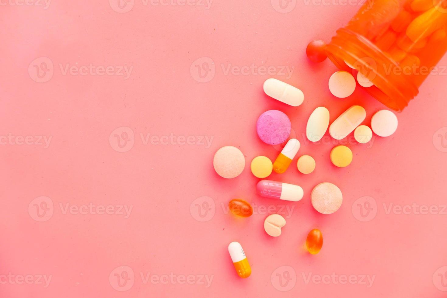 Pastillas de colores derramándose sobre fondo rosa foto