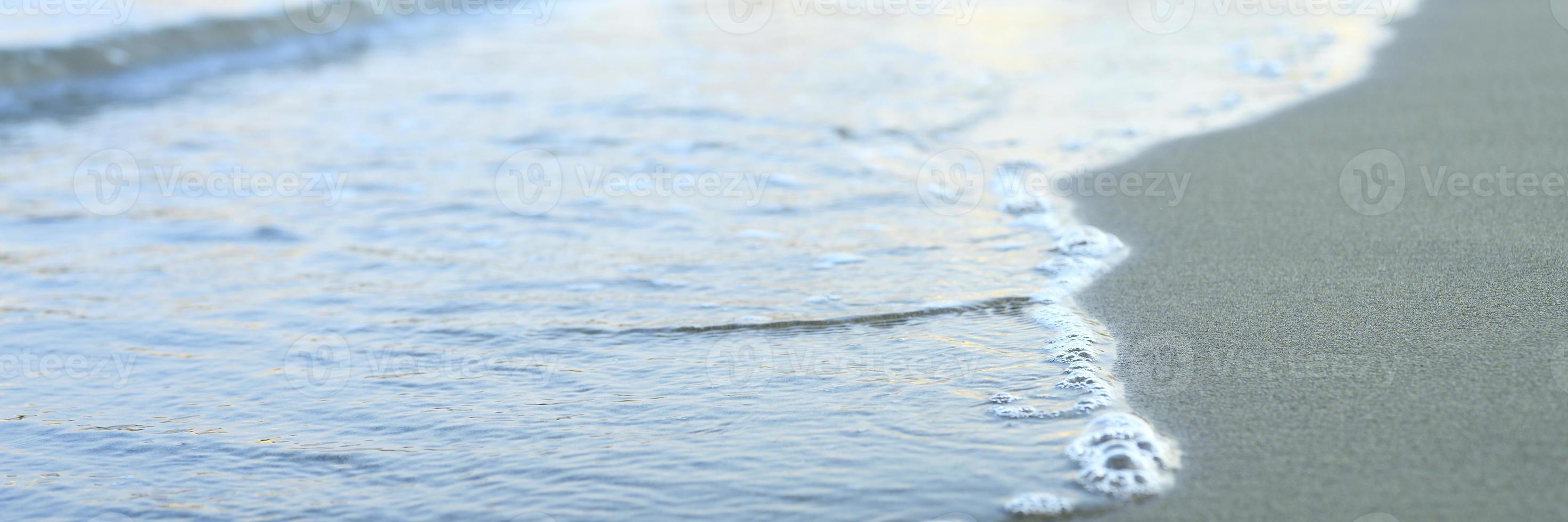 Blurred wave of the sea on the evening sand beach photo