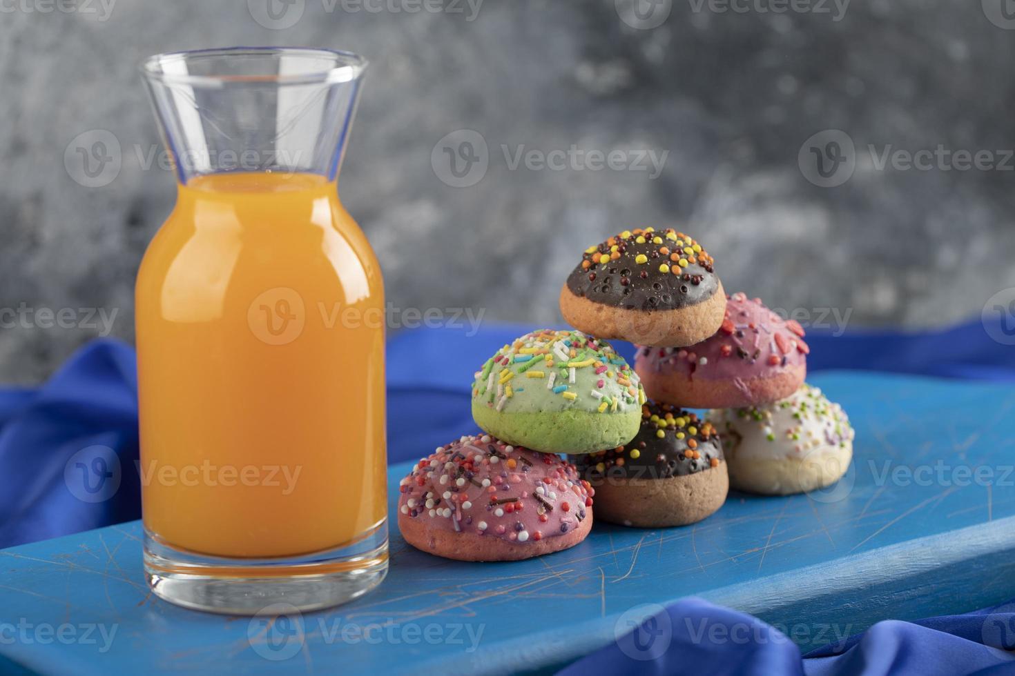 una botella de vidrio de jugo con rosquillas de colores foto