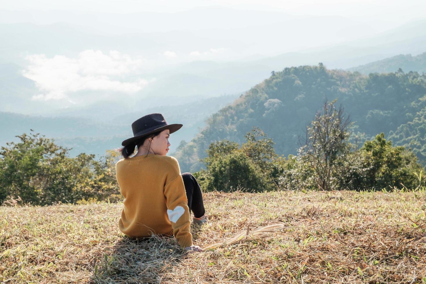 Woman sitting on a mountain photo