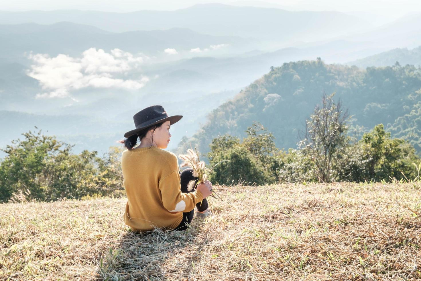 Woman holding rice while sitting on a mountain photo