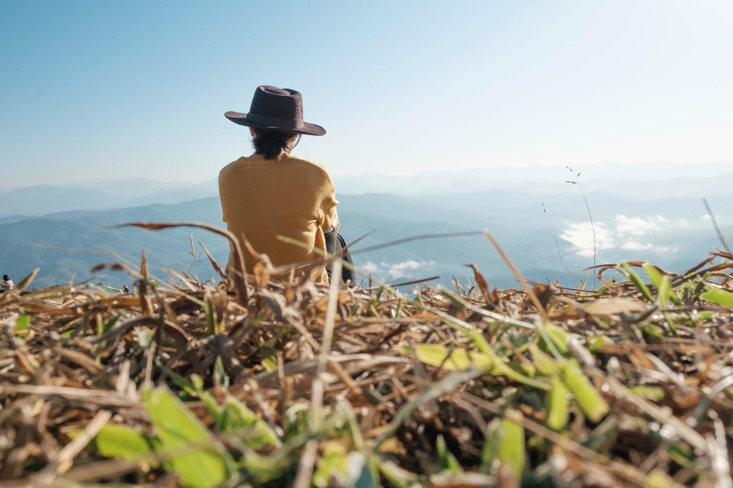 Woman sitting on a mountain during the day photo