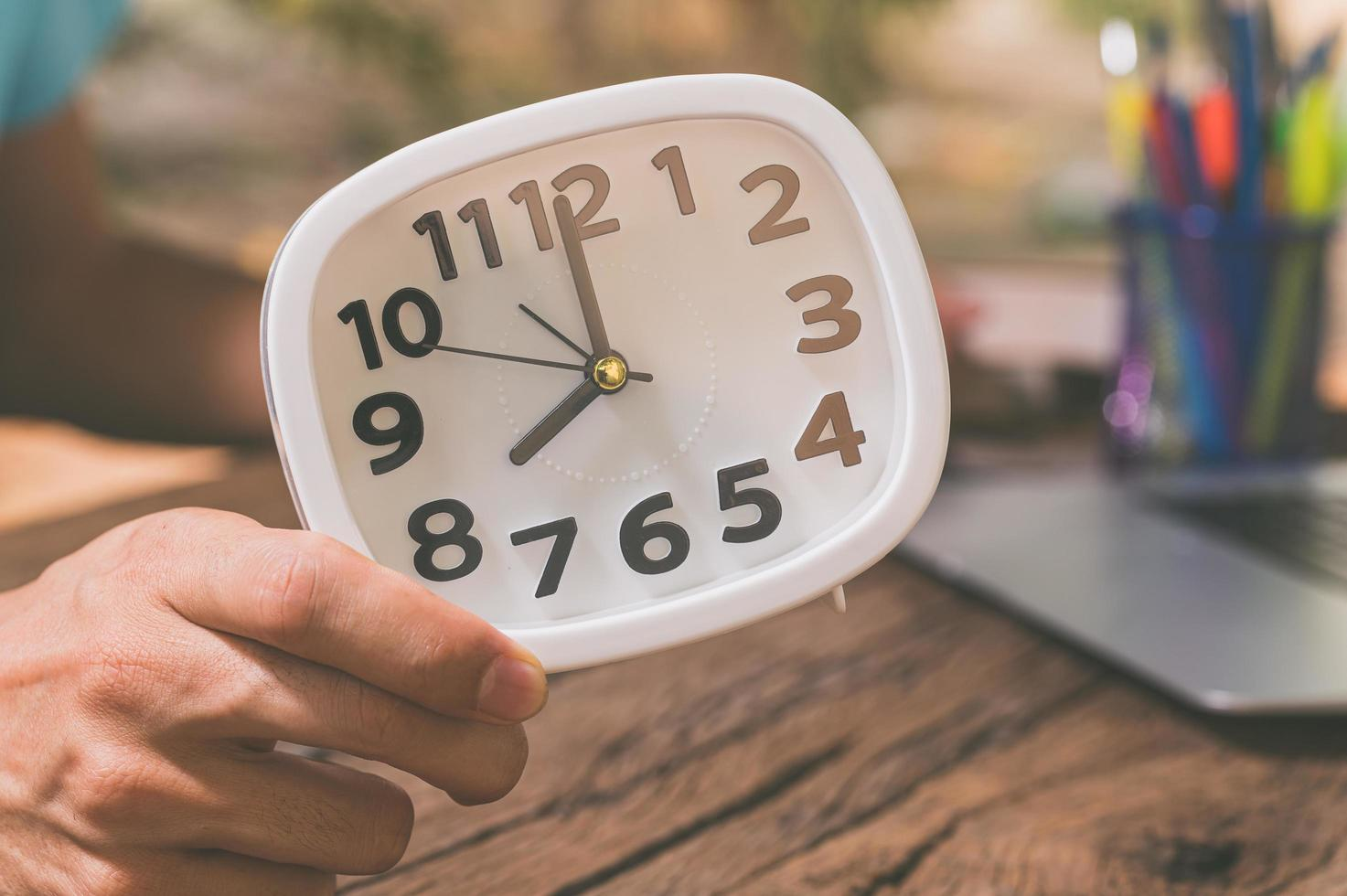 A person's hand holding a clock at a work desk photo