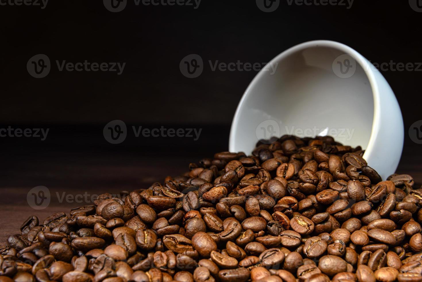Coffee bean pouring out of a white mug on wooden table photo