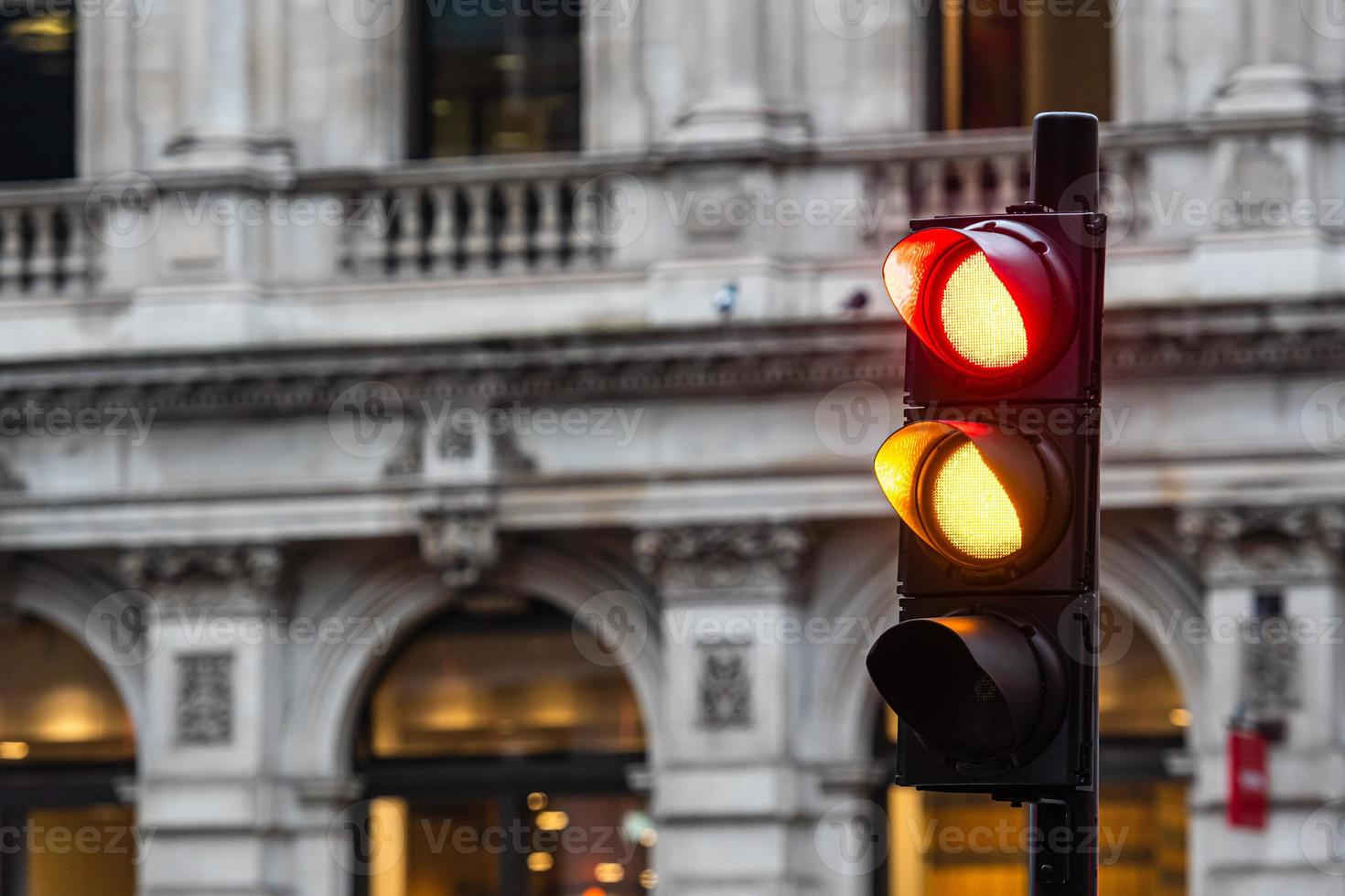 Semáforos rojos y naranjas para automóviles sobre un fondo de edificios borrosa foto