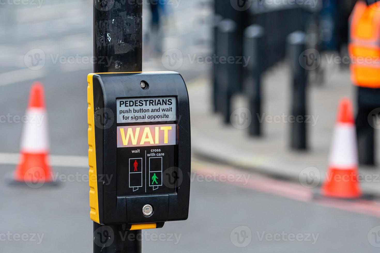 Crosswalk button for pedestrian with light warning on a defocused background photo