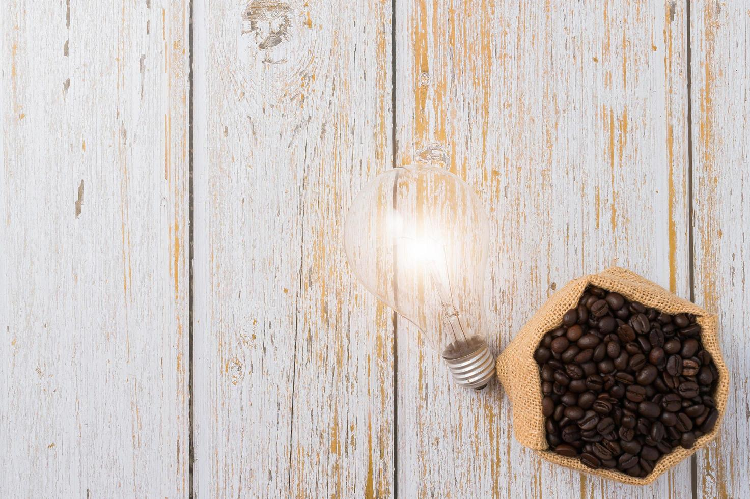 Coffee beans and a light bulb emitting energy on a wooden background photo