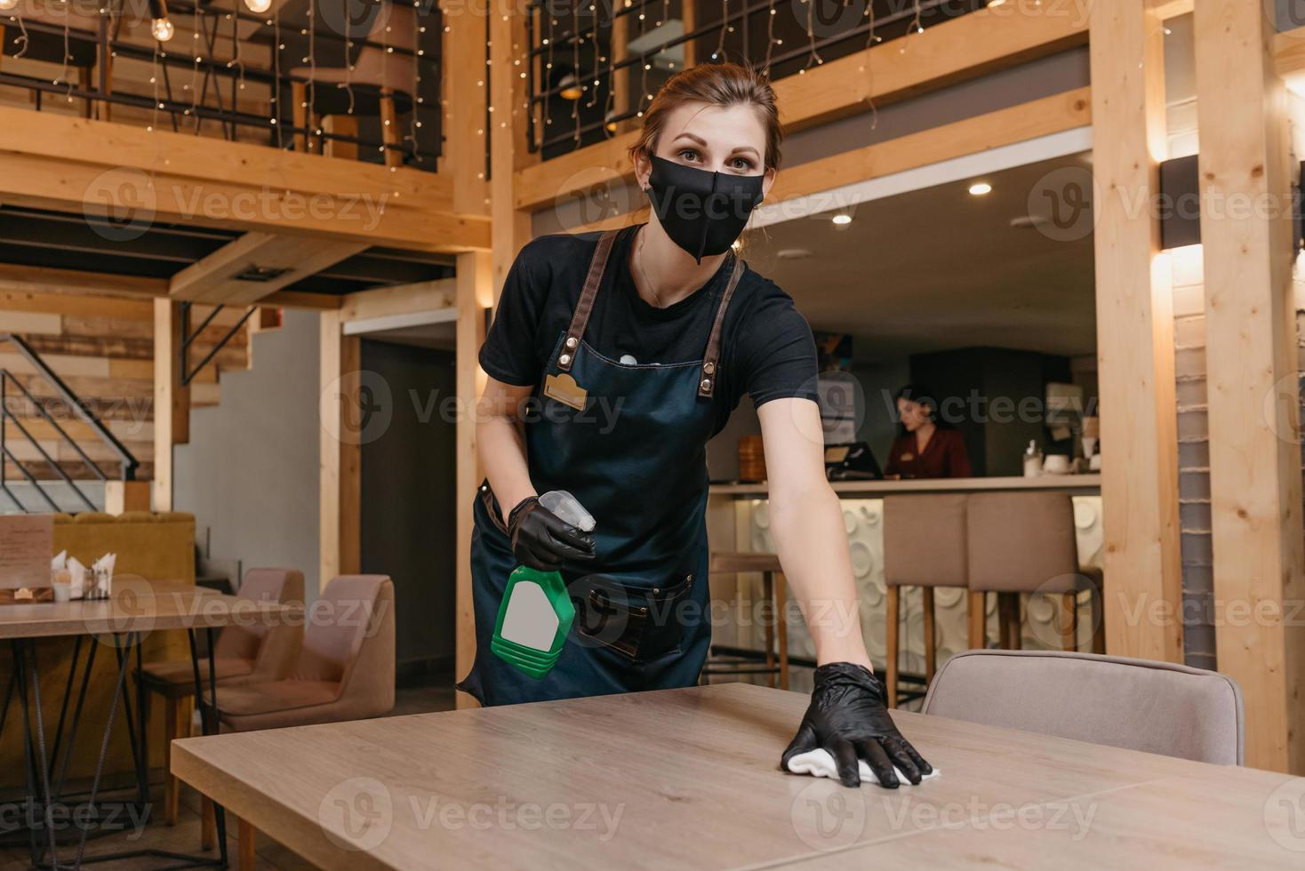 A kind waitress who wears a black medical face mask and disposable medical gloves is holding a bottle with sanitizer and cleaning tables with a rag in a restaurant photo