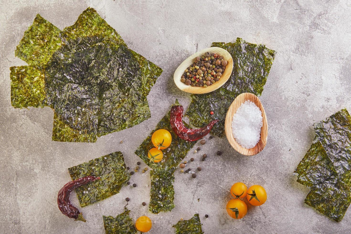 Crujiente de algas nori con tomates cherry y especias sobre hormigón gris foto