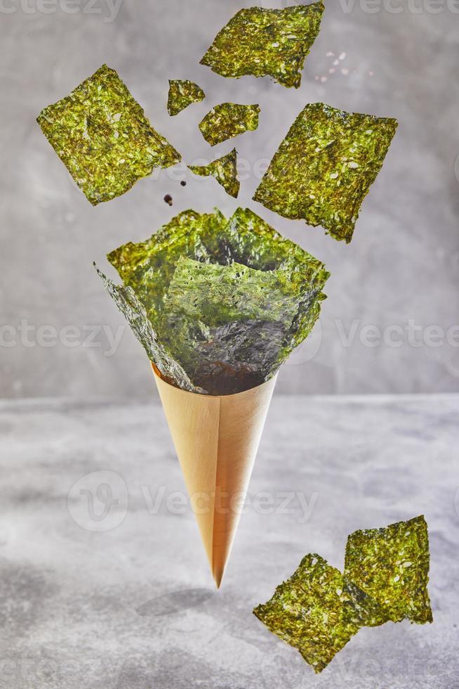 Alga nori crujiente cayendo en una taza cónica sobre un fondo gris, levitación foto