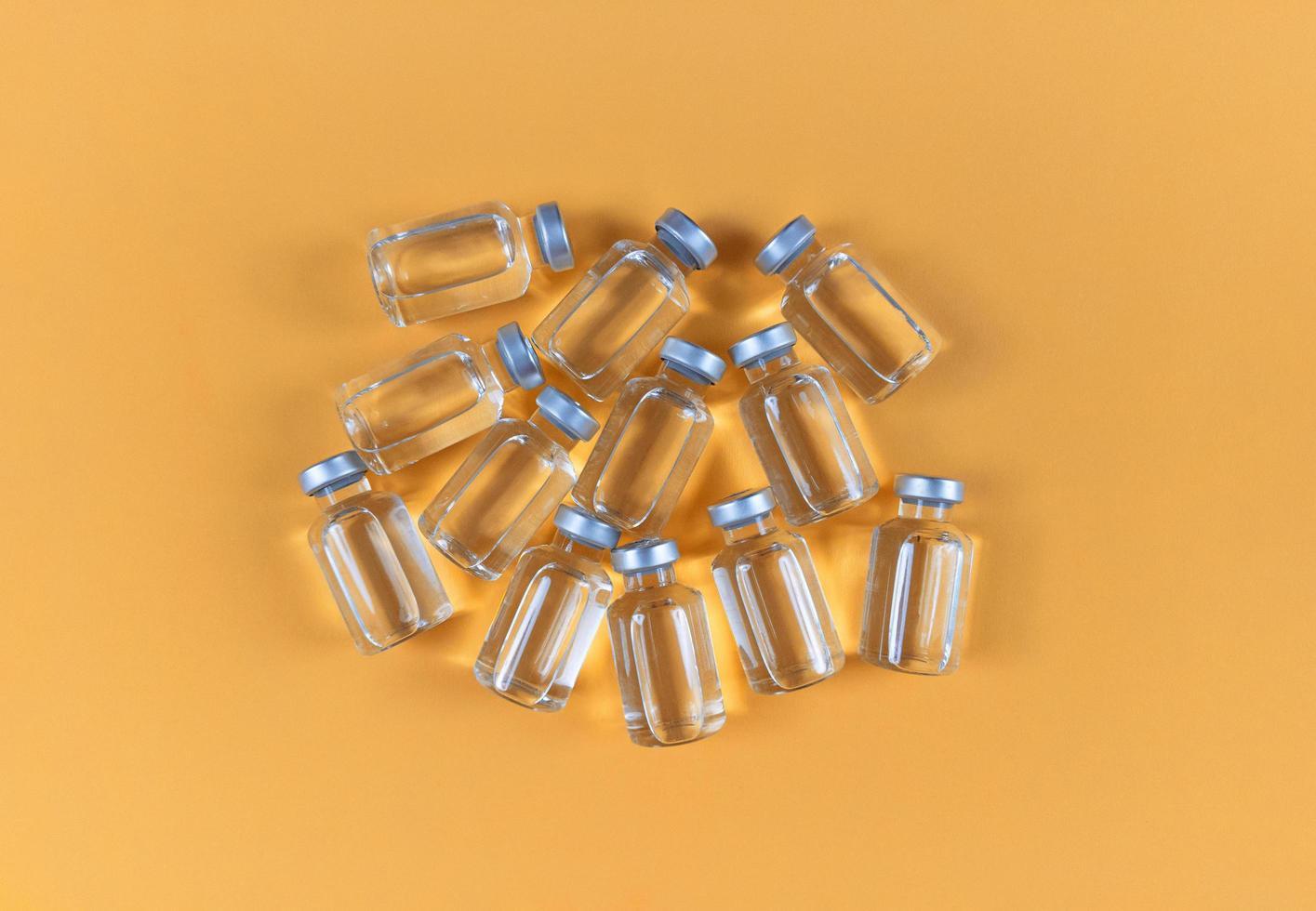 muchos viales con medicamento líquido sobre un fondo amarillo foto