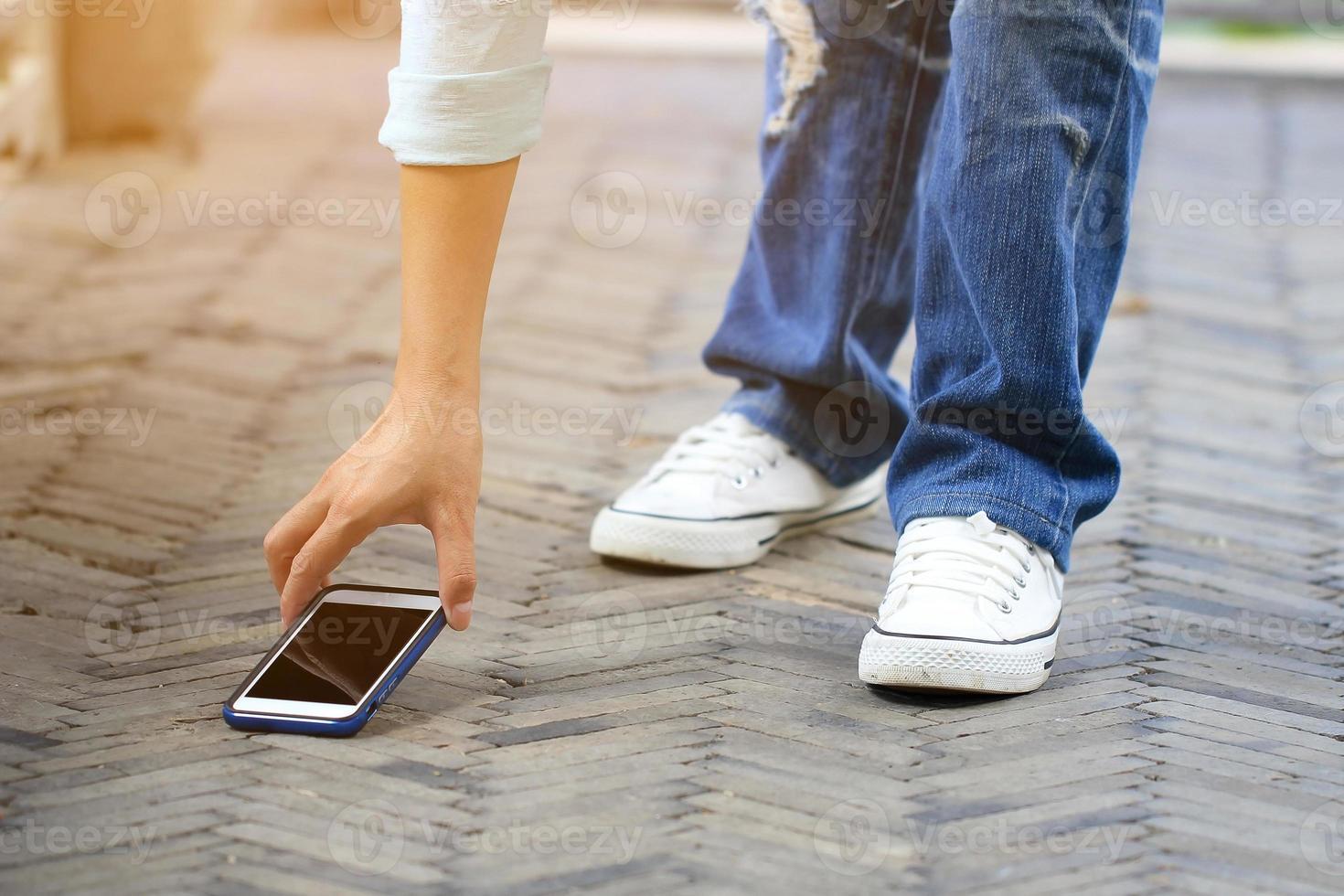 mujer recogiendo un teléfono inteligente en el suelo foto