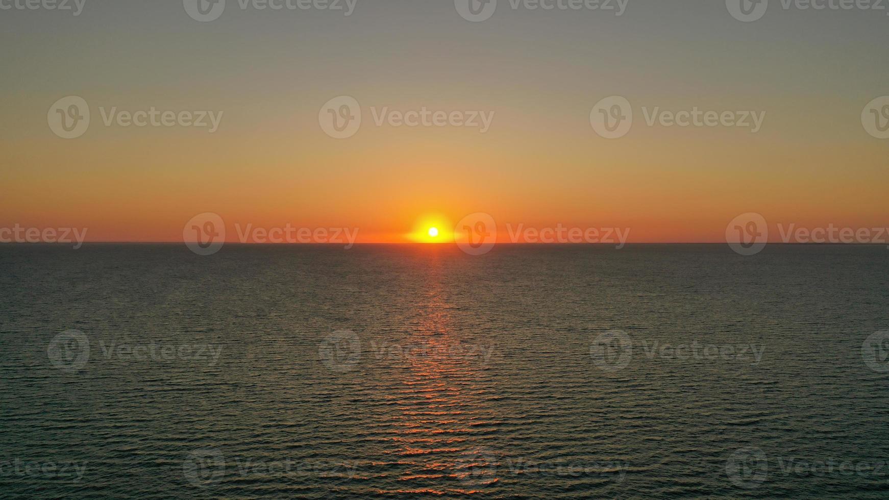 puesta de sol detrás de la línea del horizonte foto