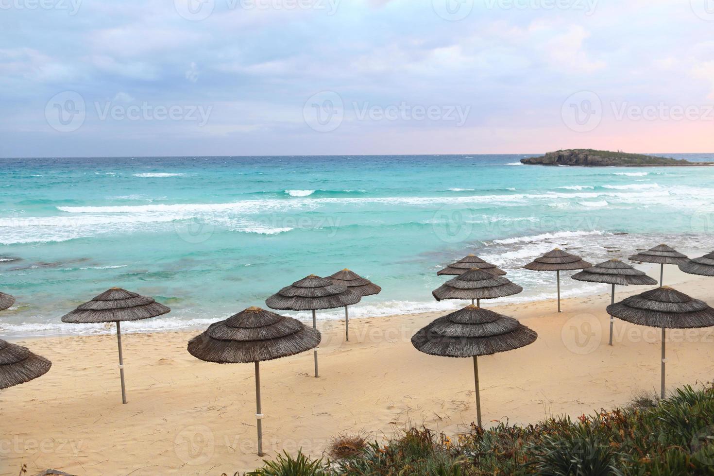 Sombrillas de paja en una playa al atardecer foto