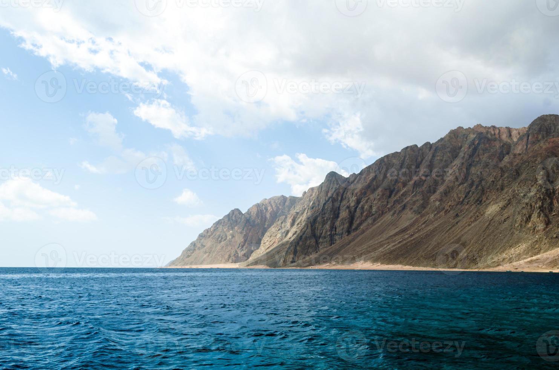 mar azul y altas montañas rocosas foto