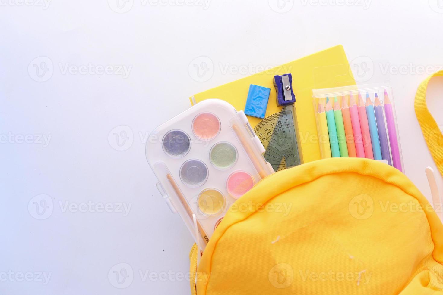 Mochila amarilla y útiles escolares sobre fondo blanco. foto
