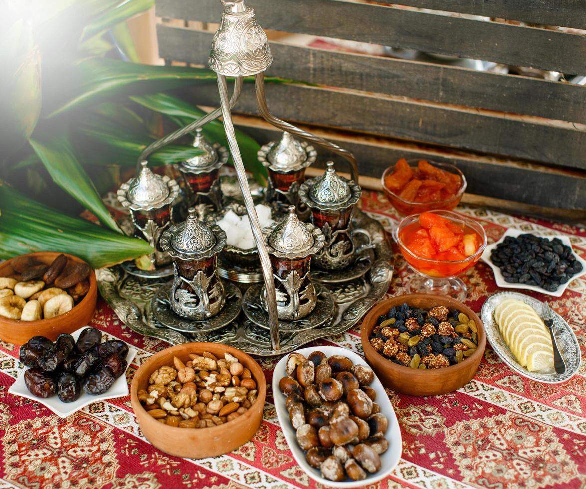 Configuración de té tradicional con bandeja de té antigua y vasos y tazones de frutas secas foto