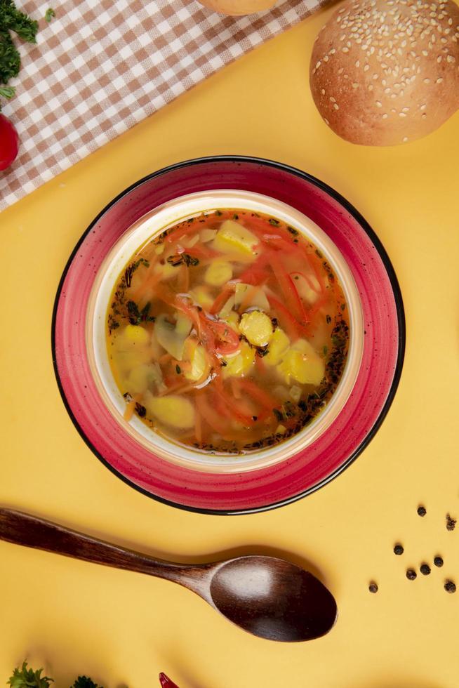 sopa de verduras con pan de sésamo y cuchara de madera foto