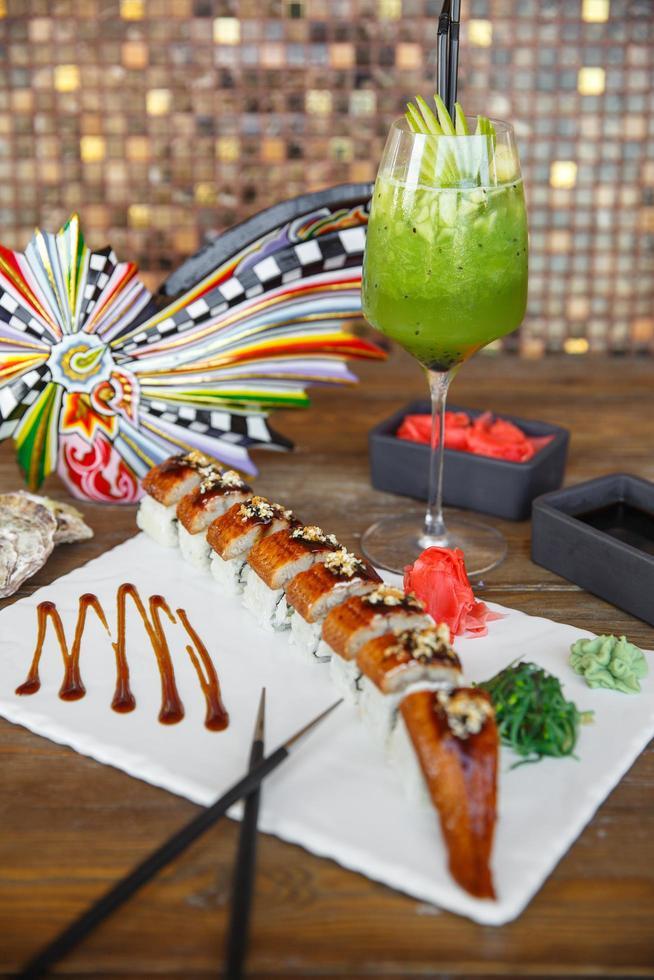 Rollos de sushi unagi servidos en una placa de piedra blanca con cóctel de kiwi foto