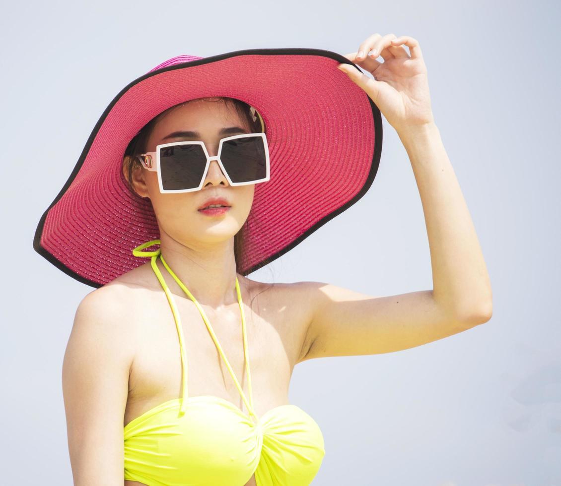 Mujer asiática se relaja en las vacaciones de verano en la playa. foto