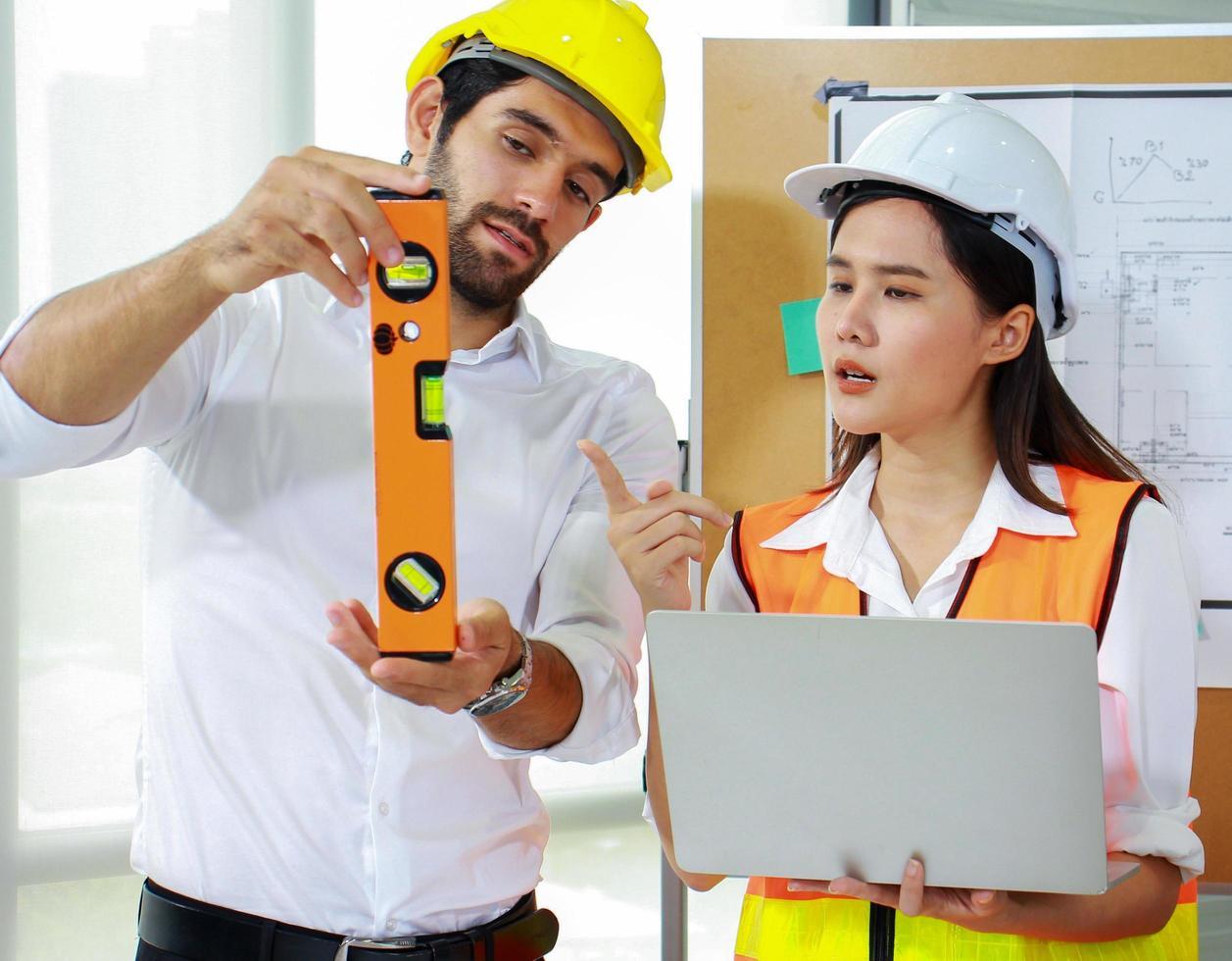 Los ingenieros discuten el proyecto mientras sostienen una computadora portátil. foto