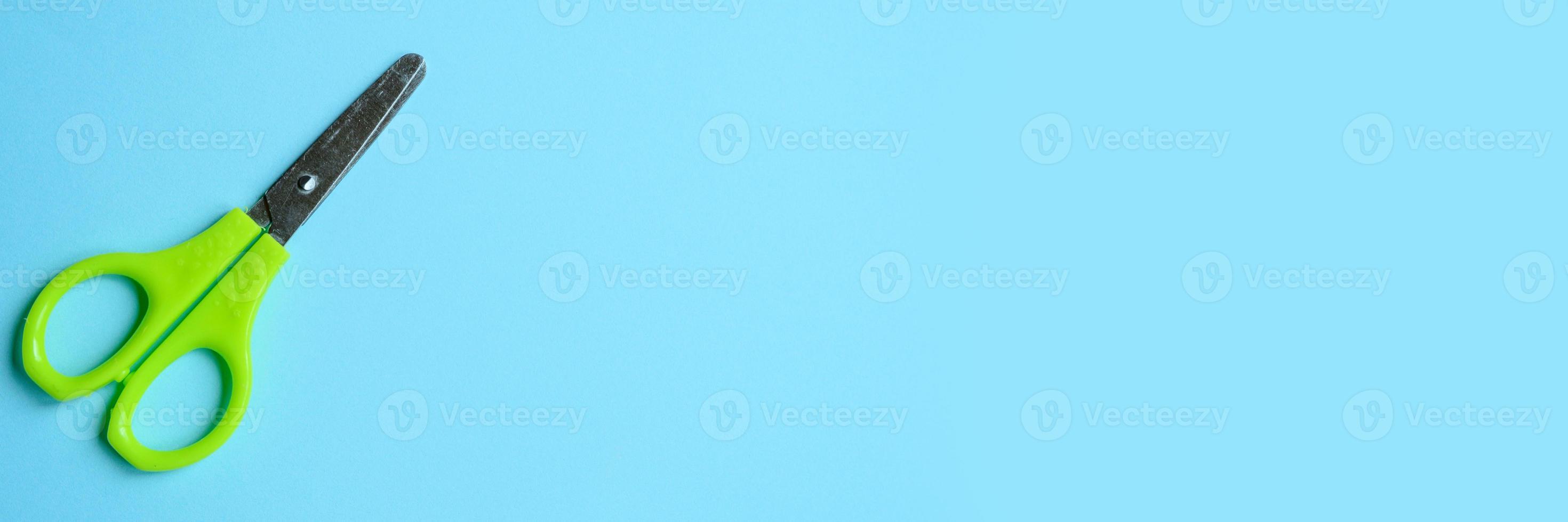 Tijeras de oficina pequeña sobre fondo azul. foto