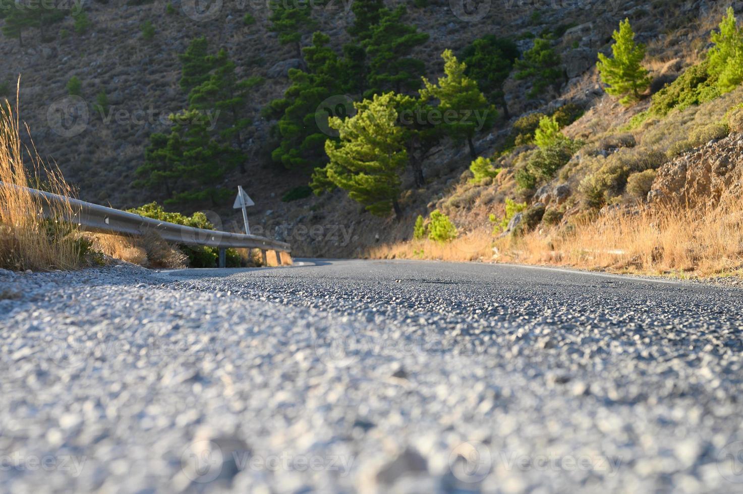 un camino sinuoso en las montañas con puesta de sol en la hora dorada foto