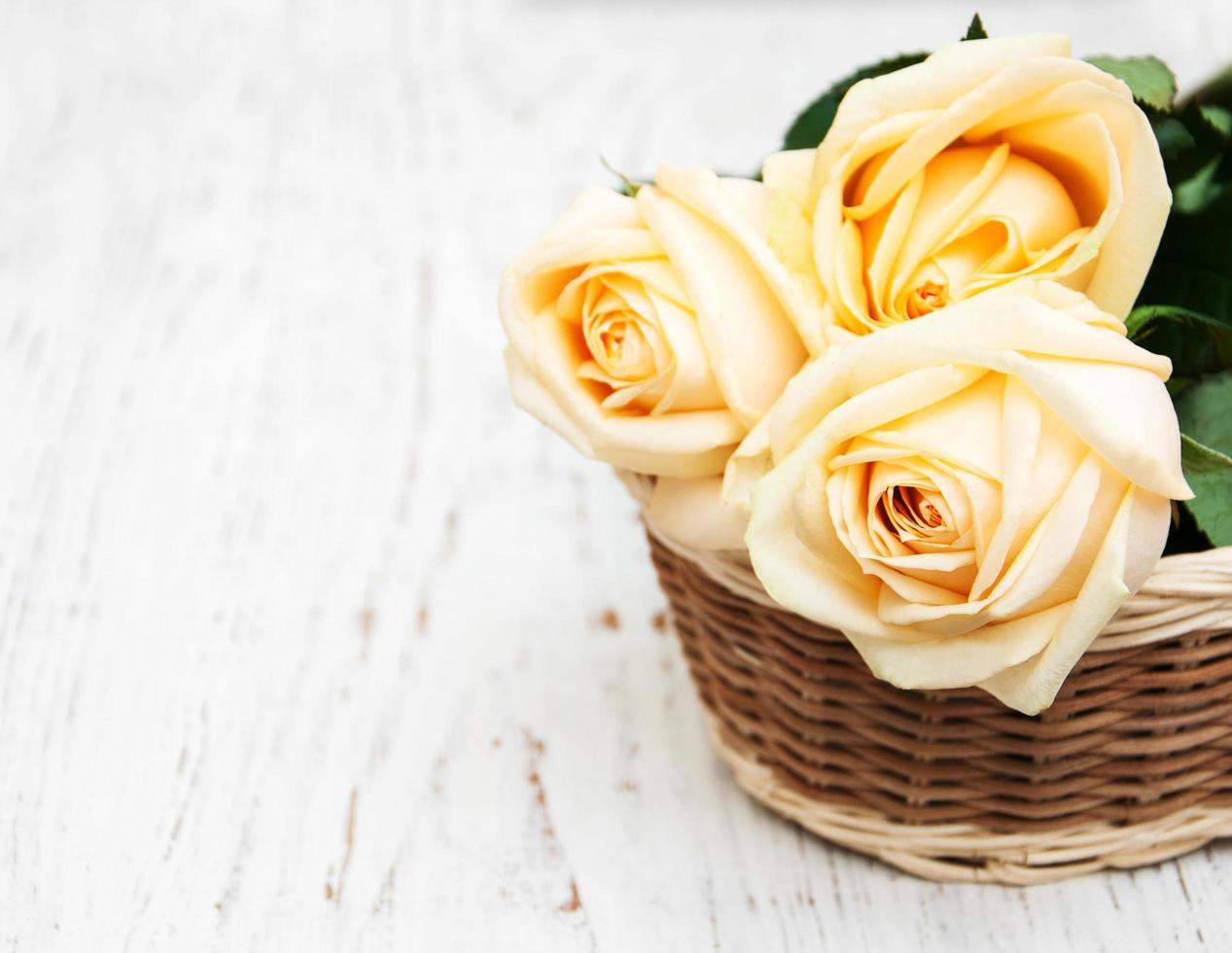 Basket with roses on an old wooden table photo